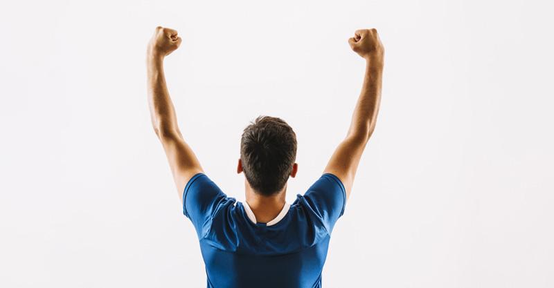 Deportista con camiseta azul oscura posa de espaldas celebrando una victoria